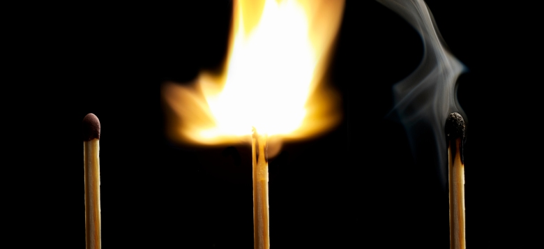 Matchstick burning on black background
